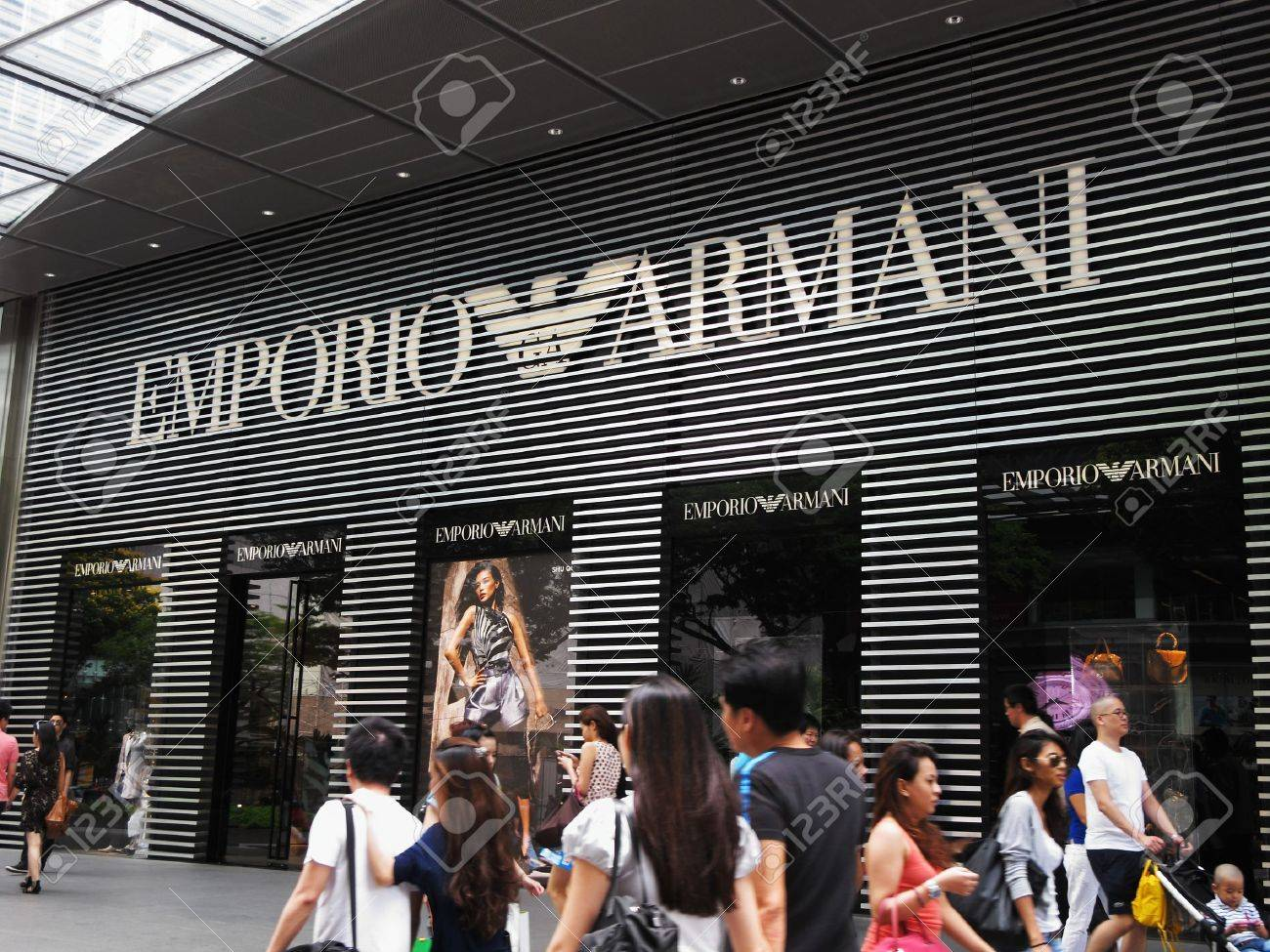 outside Mandarin Gallery mall at Orchard Road in Singapore, February 27, 2011 - shoppers walking along a pavement in front of an Emporio Armani display Stock Photo - 8944886