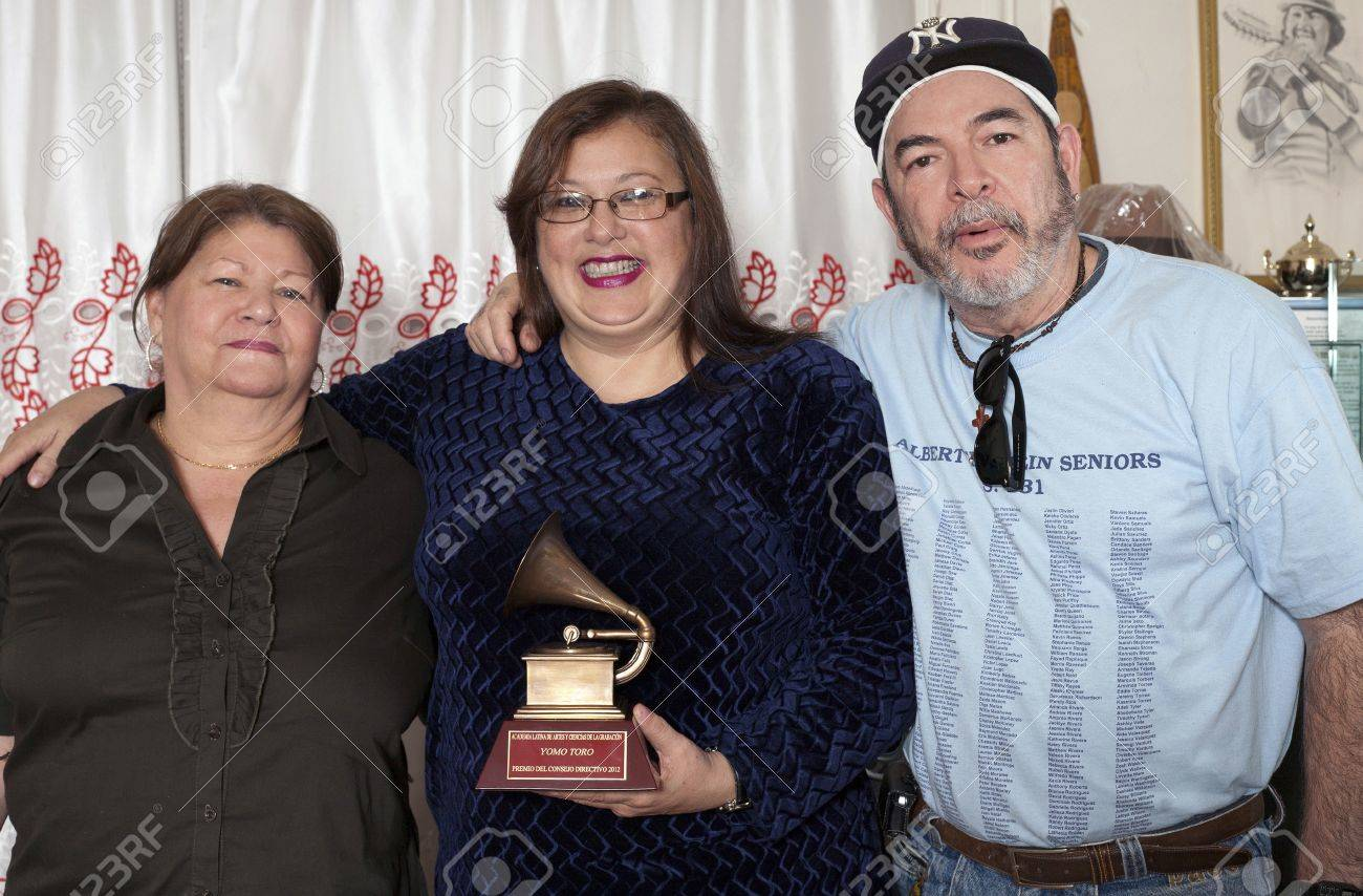 BRONX, NEW YORK - DECEMBER 23: Yomo Toro's brother Angel, Yomo's wife Minerva center and Angel's wife left, unite to  remember international cuatro player Yomo Toro who was awarded the Latin Grammy but passed away before he could accept it. Taken December Stock Photo - 17262510
