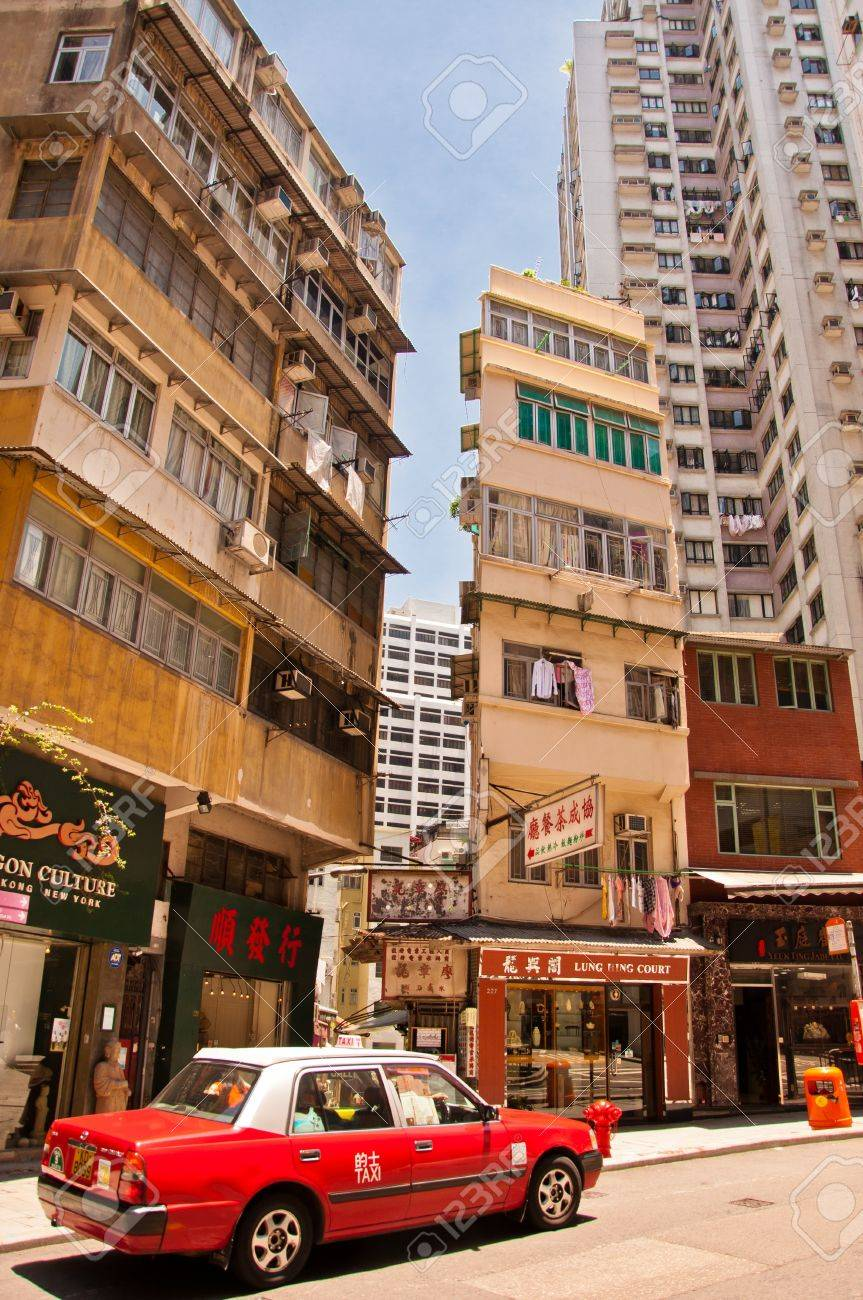 Hong Kong S.A.R., China - July 30, 2012: Street view with typical taxi, shops and tall buildings on July 30, 2012 in Hong Kong, China. With 7M population and land mass of 1104 sq km, it is one of the most dense areas in the world. Stock Photo - 15156349