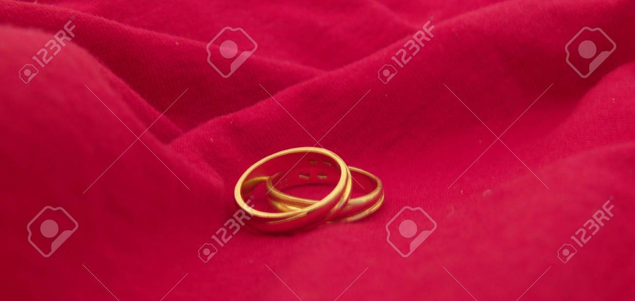 Two Wedding Rings On A Red Cloth Background Stock Photo Picture And