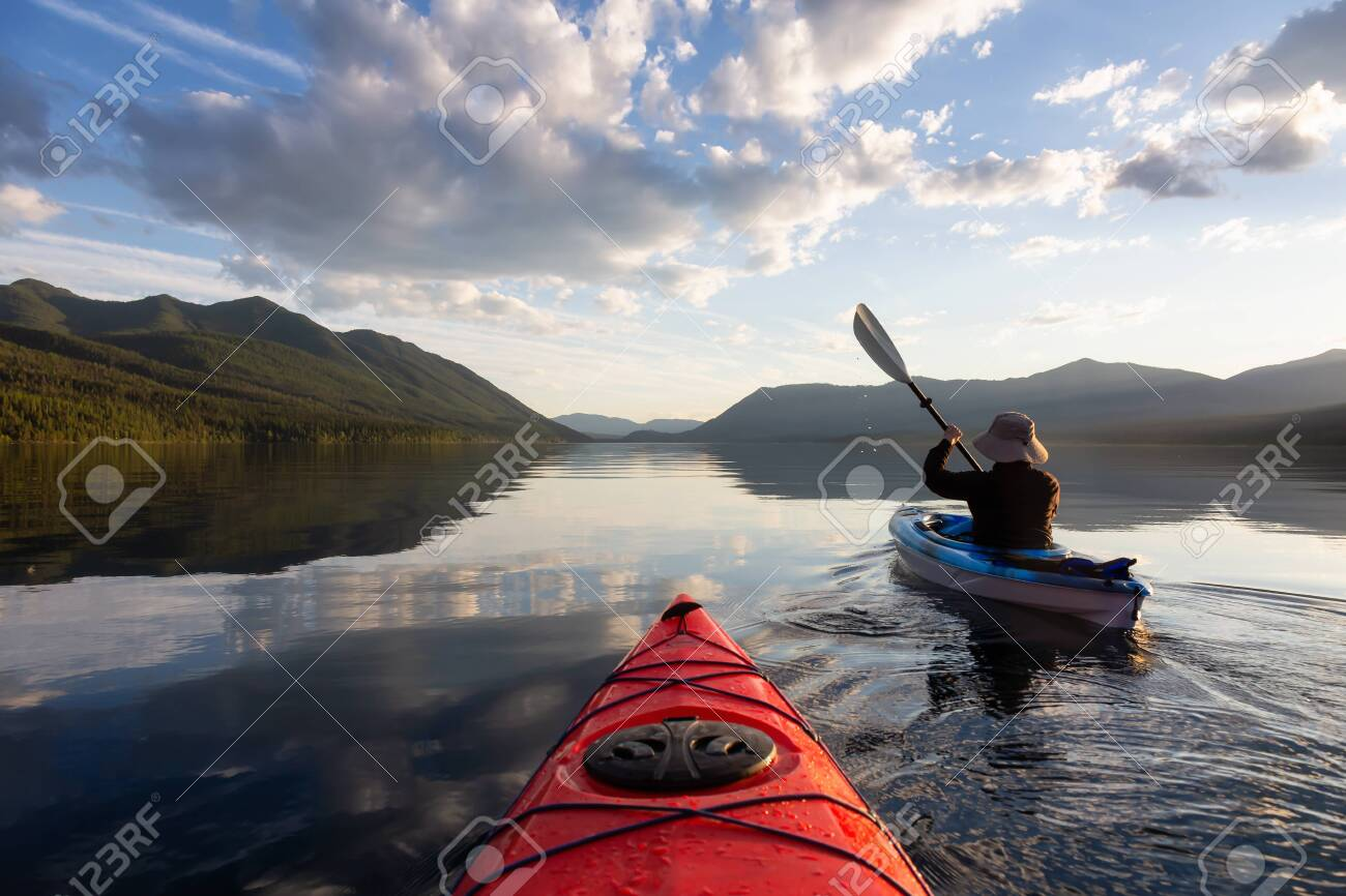 Adventurous Man Kayaking in Lake McDonald during a sunny summer evening with American Rocky Mountains in the background. Taken in Glacier National Park, Montana, USA. - 137966252