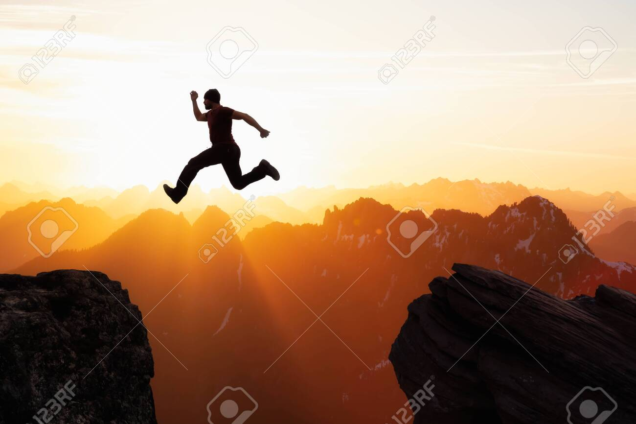 Adventure and Challenge Concept Composite of Man Jumping Across a Gap between the Cliffs in the Mountains. Landscape from British Columbia, Canada. - 148254278