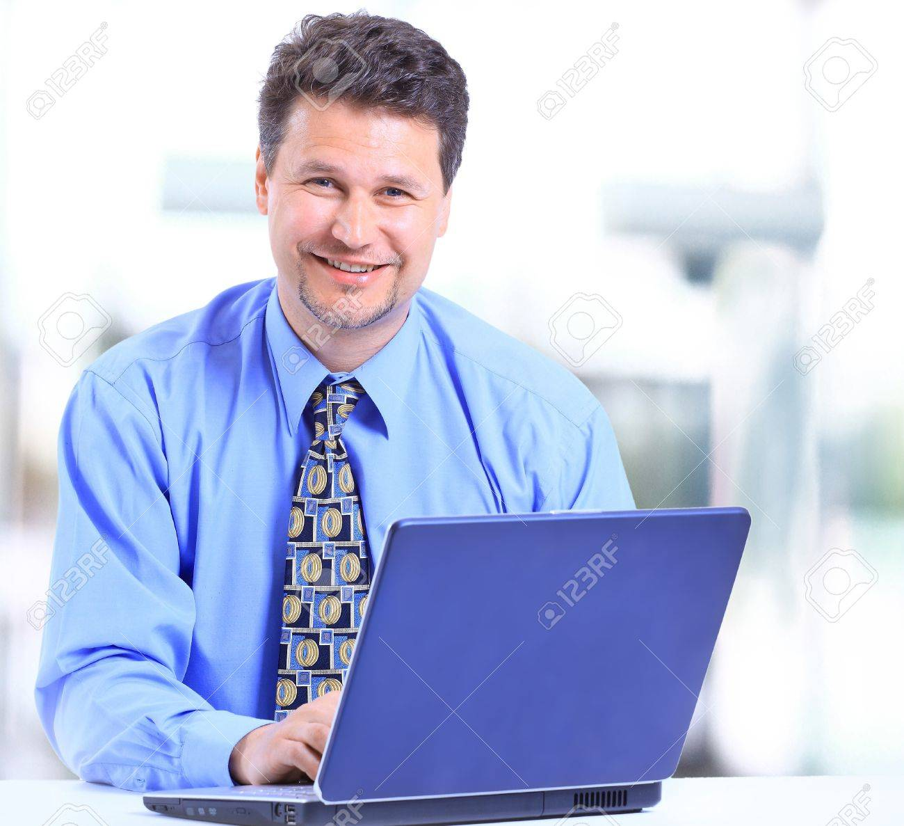Happy executive sitting in front of laptop with arms folded Stock Photo - 11315761