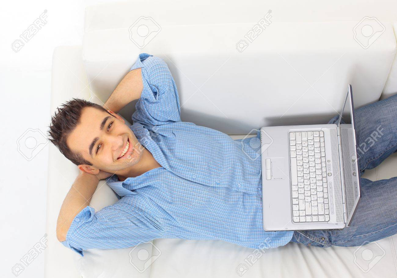 Portrait Of A Young Guy Relaxing On Couch With A Laptop Stock ...
