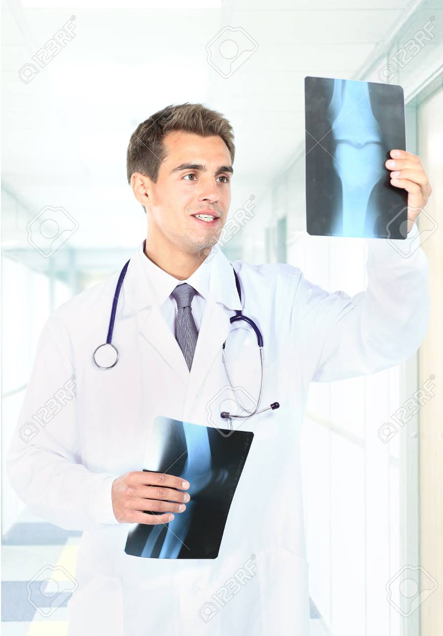 Happy doctor looking at x-ray Stock Photo - 22335429