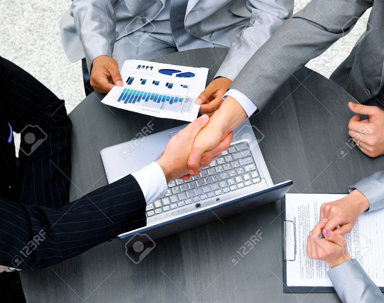Business people shaking hands, finishing up a meeting - 22518125