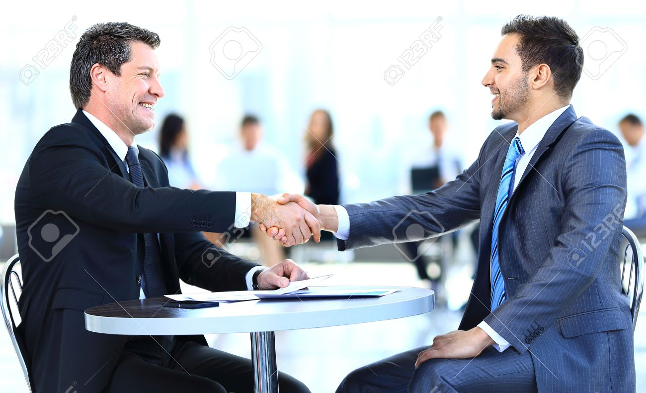 Business colleagues sitting at a table during a meeting with two male executives shaking hands Standard-Bild - 29170008