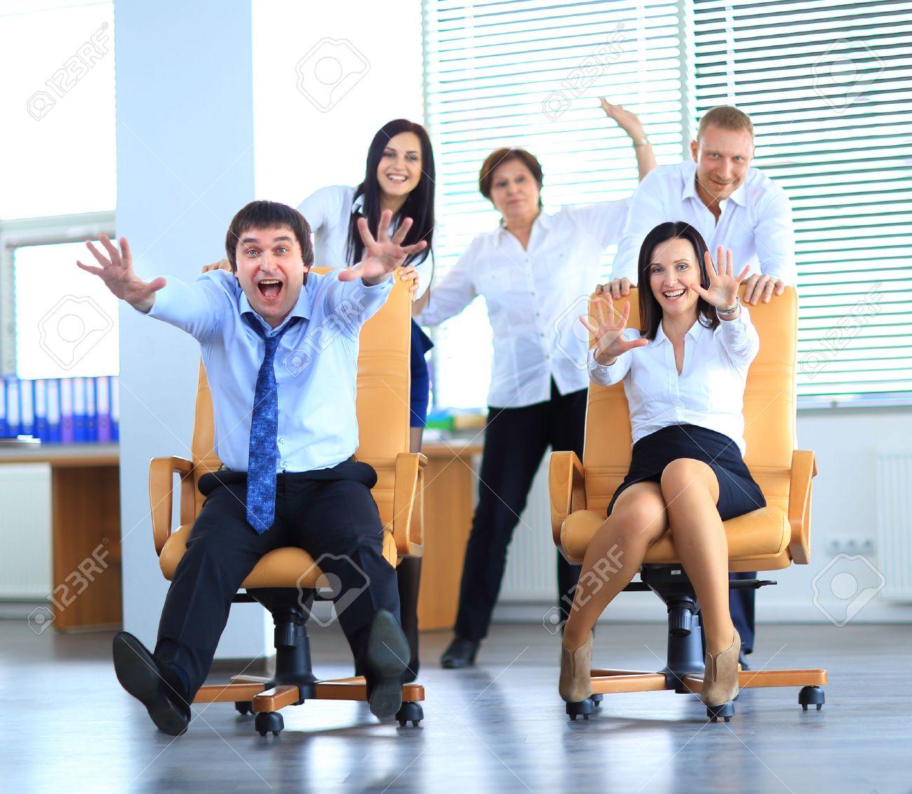 Happy office employees having fun at work in an office chair race Standard-Bild - 29170065