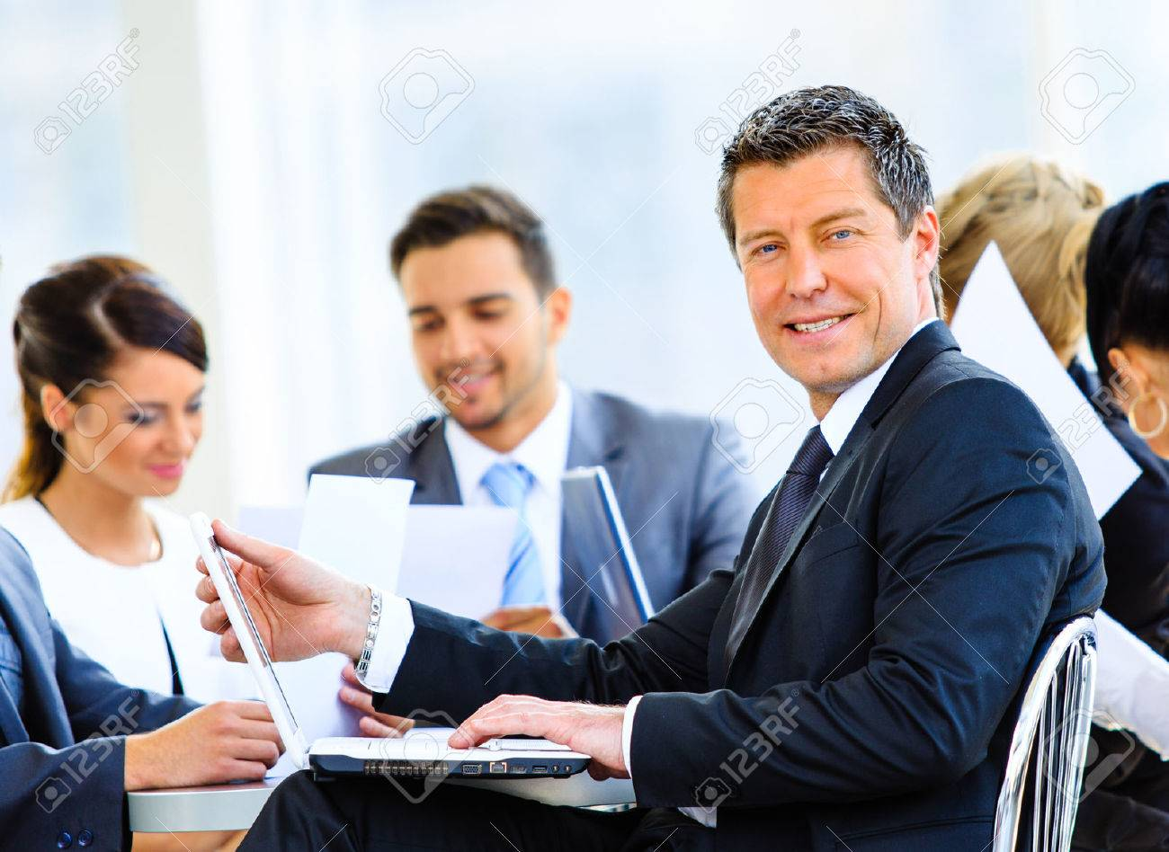Portrait of young handsome businessman in office with colleagues in the background Standard-Bild - 34354306