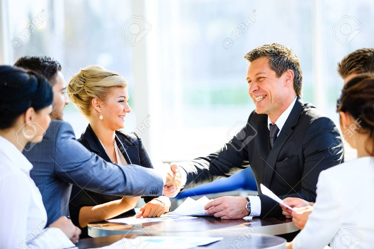 Mature businessman shaking hands to seal a deal with his partner and colleagues in a modern office Standard-Bild - 34323942