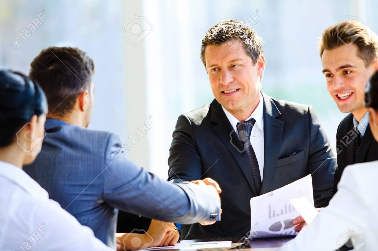 Business colleagues sitting at a table during a meeting with two male executives shaking hands Standard-Bild - 34323943
