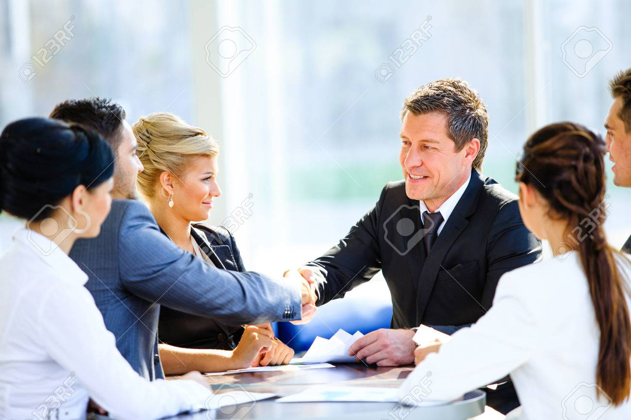 Business colleagues sitting at a table during a meeting with two male executives shaking hands Standard-Bild - 48295241