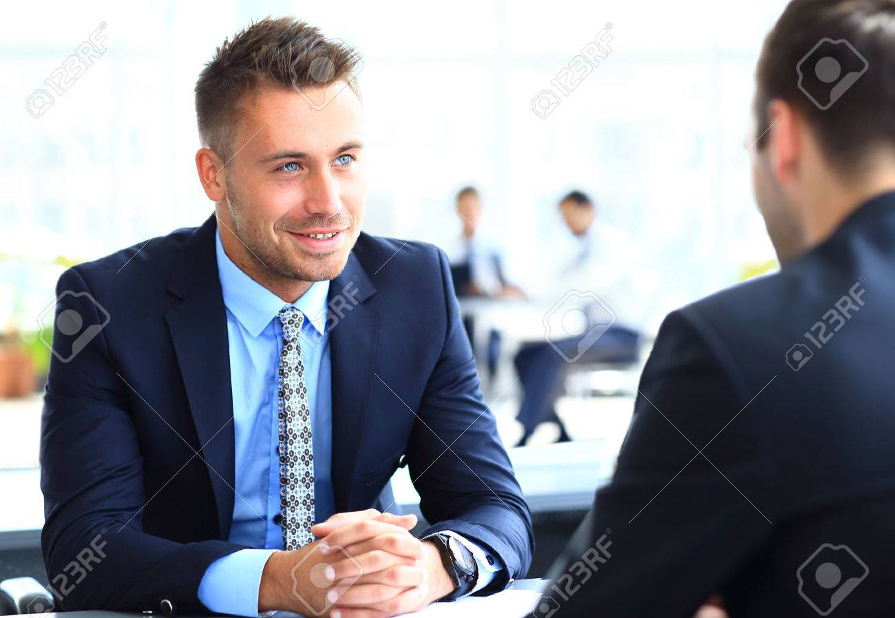 Image of smart businessman explaining new strategy to his partner at meeting Standard-Bild - 49499117