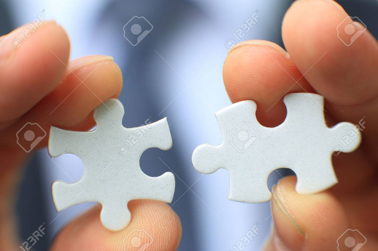 Businessman holding two blank white puzzle pieces in his hands conceptual of solving a problem, growth and development. Standard-Bild - 56489820