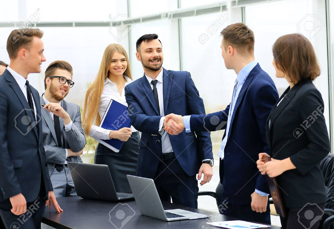 Group of confident business people in formalwear sitting at the table together and smiling while two men handshaking Standard-Bild - 57049807