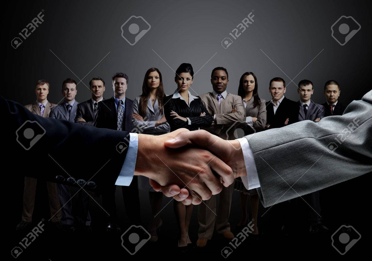 closeup of handshake of business partners on the background of a professional business team on a dark background.the photo has a empty space for your text Standard-Bild - 66015193