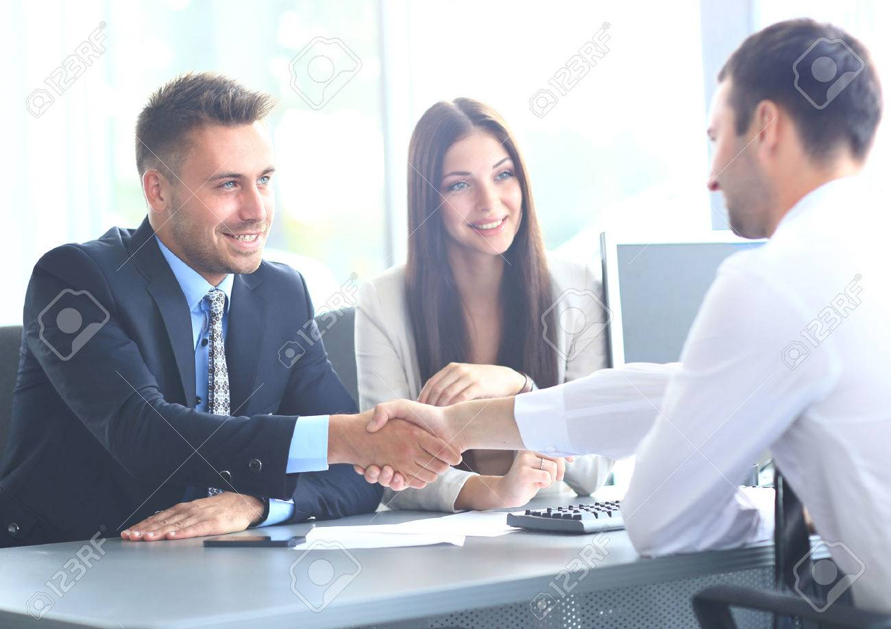 Business people shaking hands, finishing up a meeting - 67388055