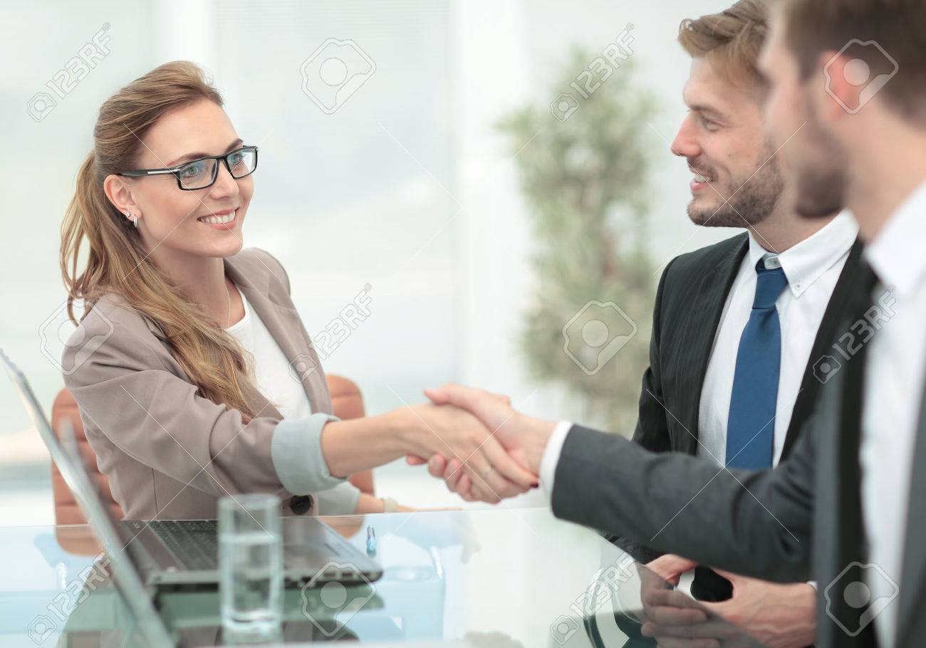 Happy smiling business people shaking hands after a deal in offi - 80121812