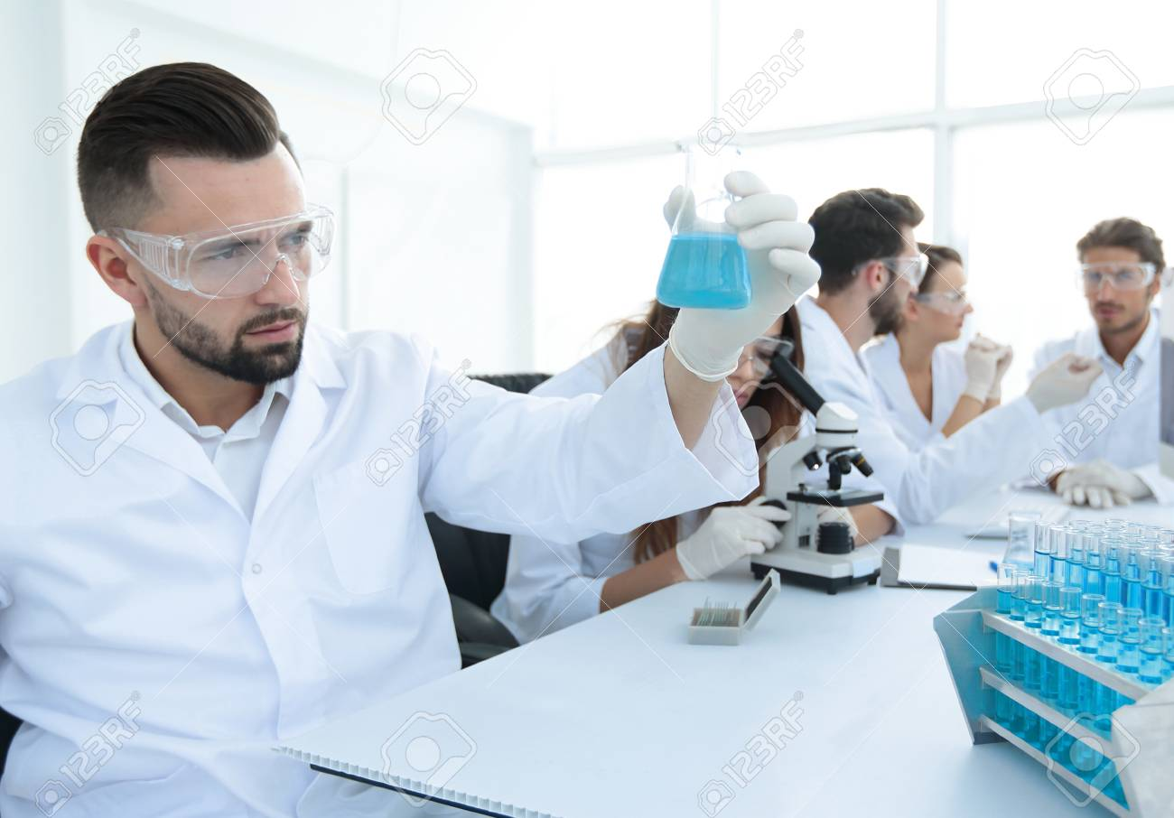 Biochemist With Flask Petri Sitting At A Desk Stock Photo Picture