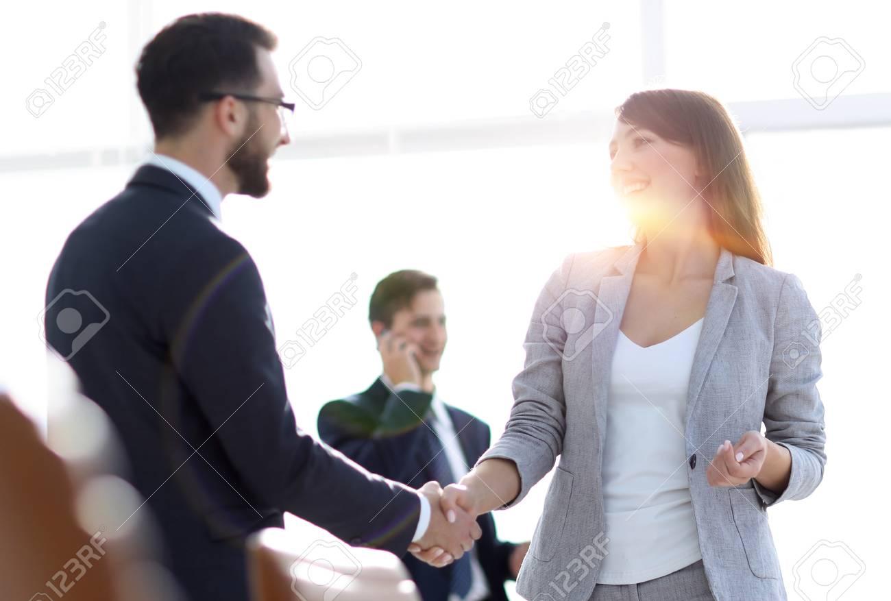 handshake between colleagues in the workplace - 107455767