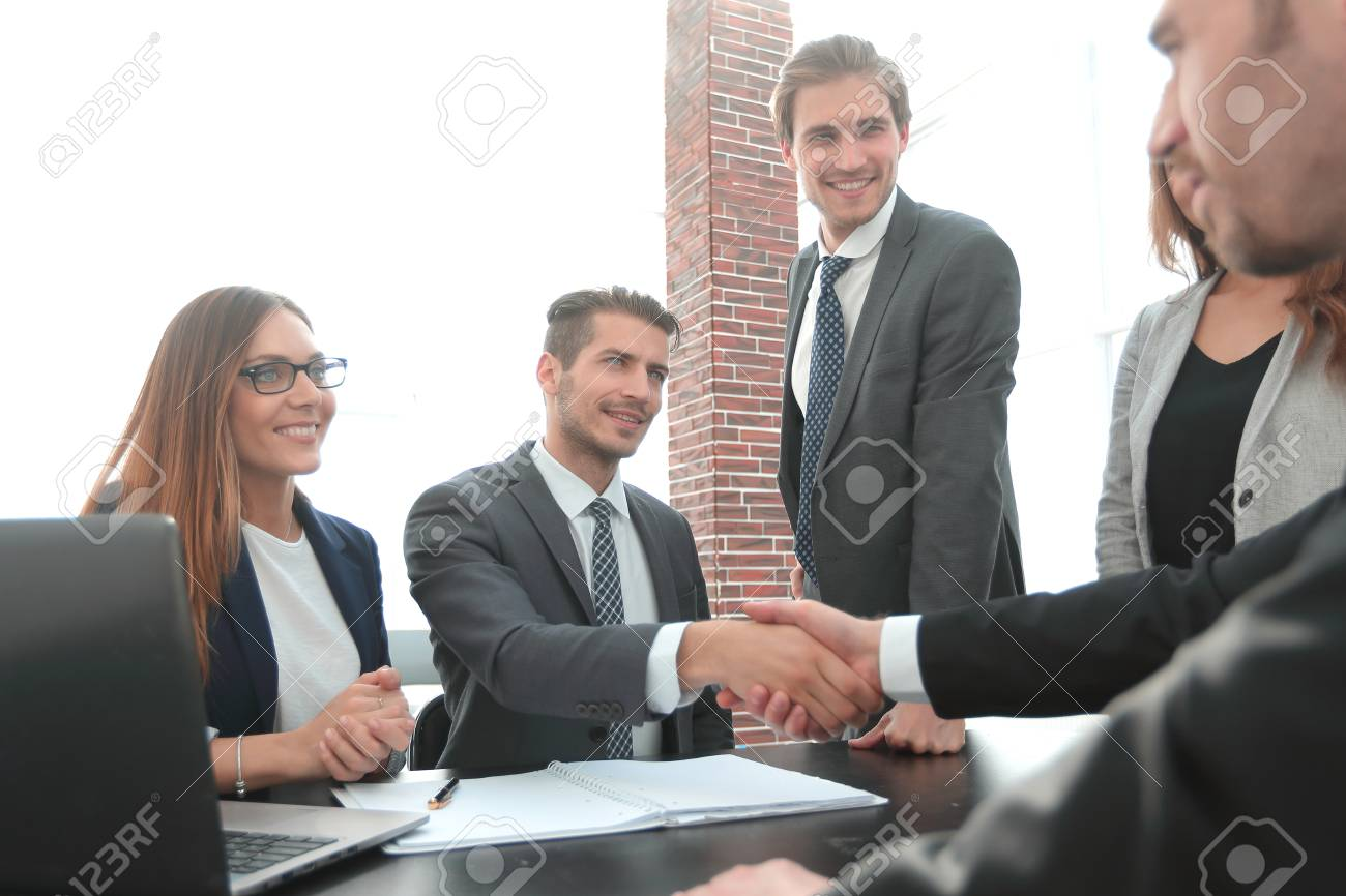 shaking hands after a business meeting in the office - 115186336