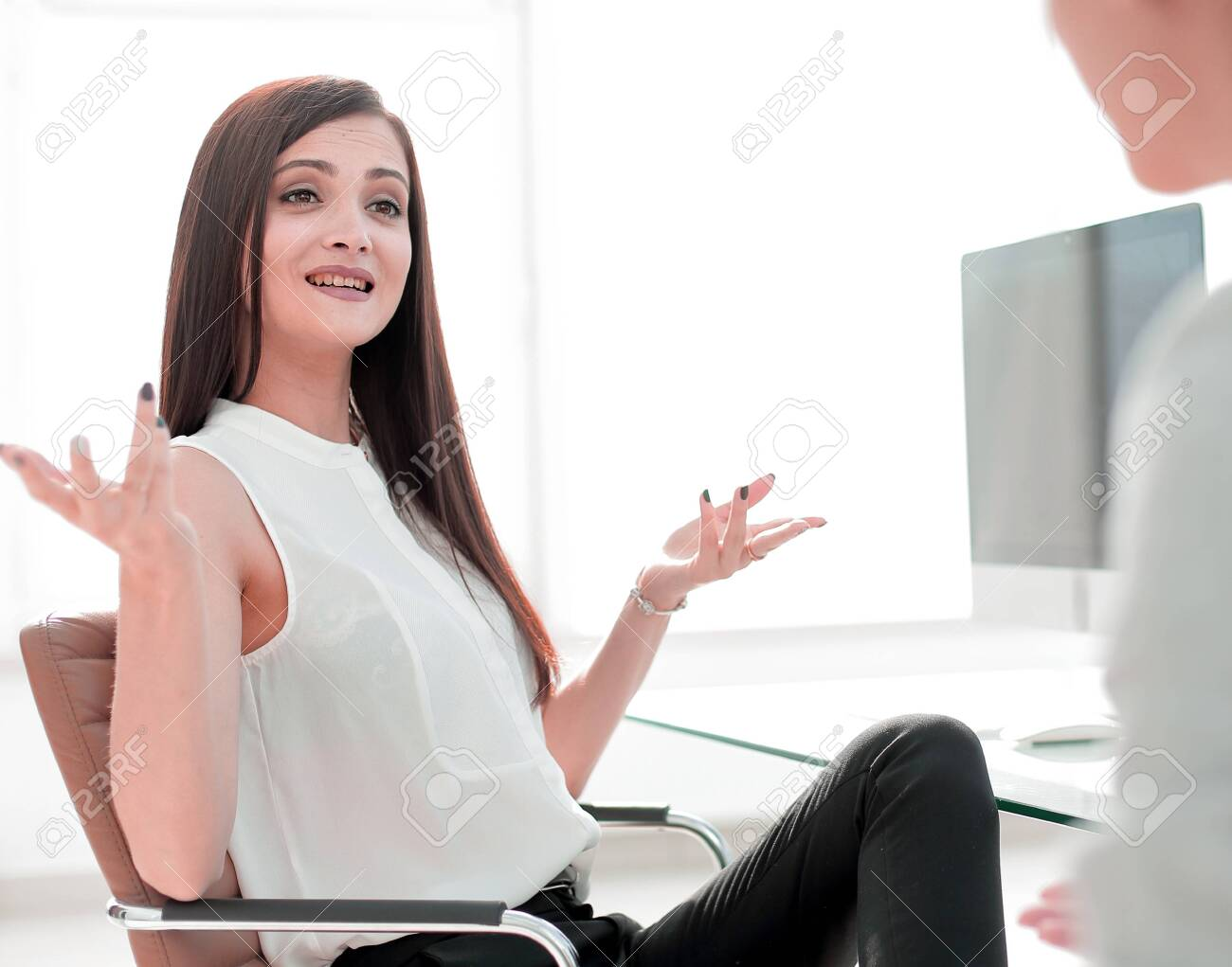 two business women talking in the workplace - 120458702