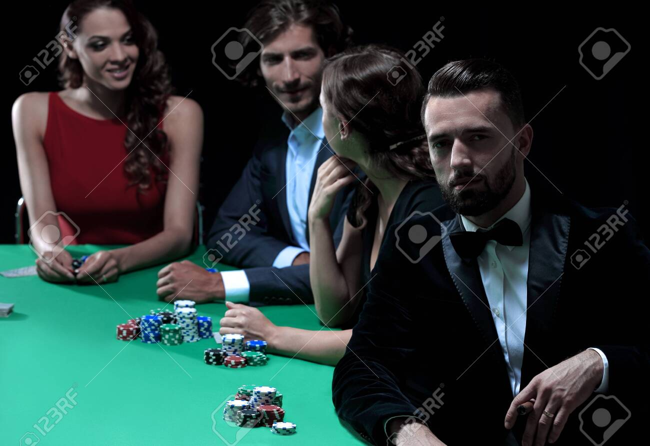 Man with cigar looking up from poker game in casino - 132488622