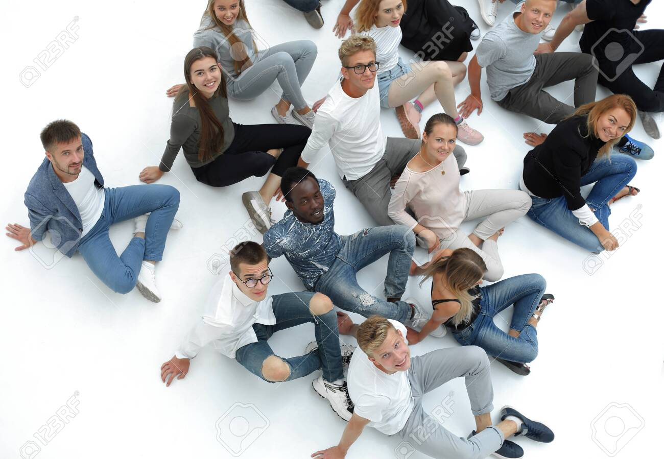 group of young people sitting on the floor and looking at the camera. - 141529404