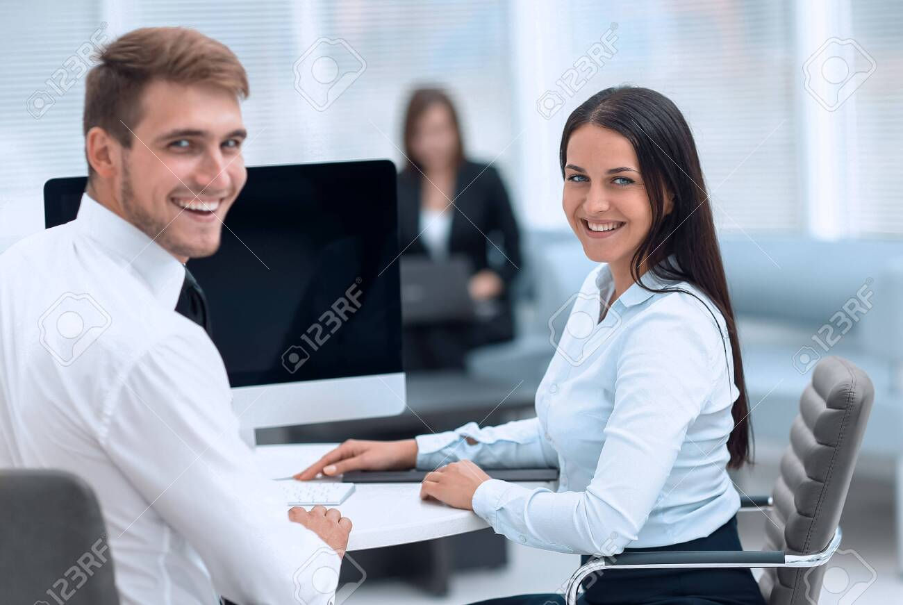 members of the business team sitting at Desk and looking at camera . - 143741253