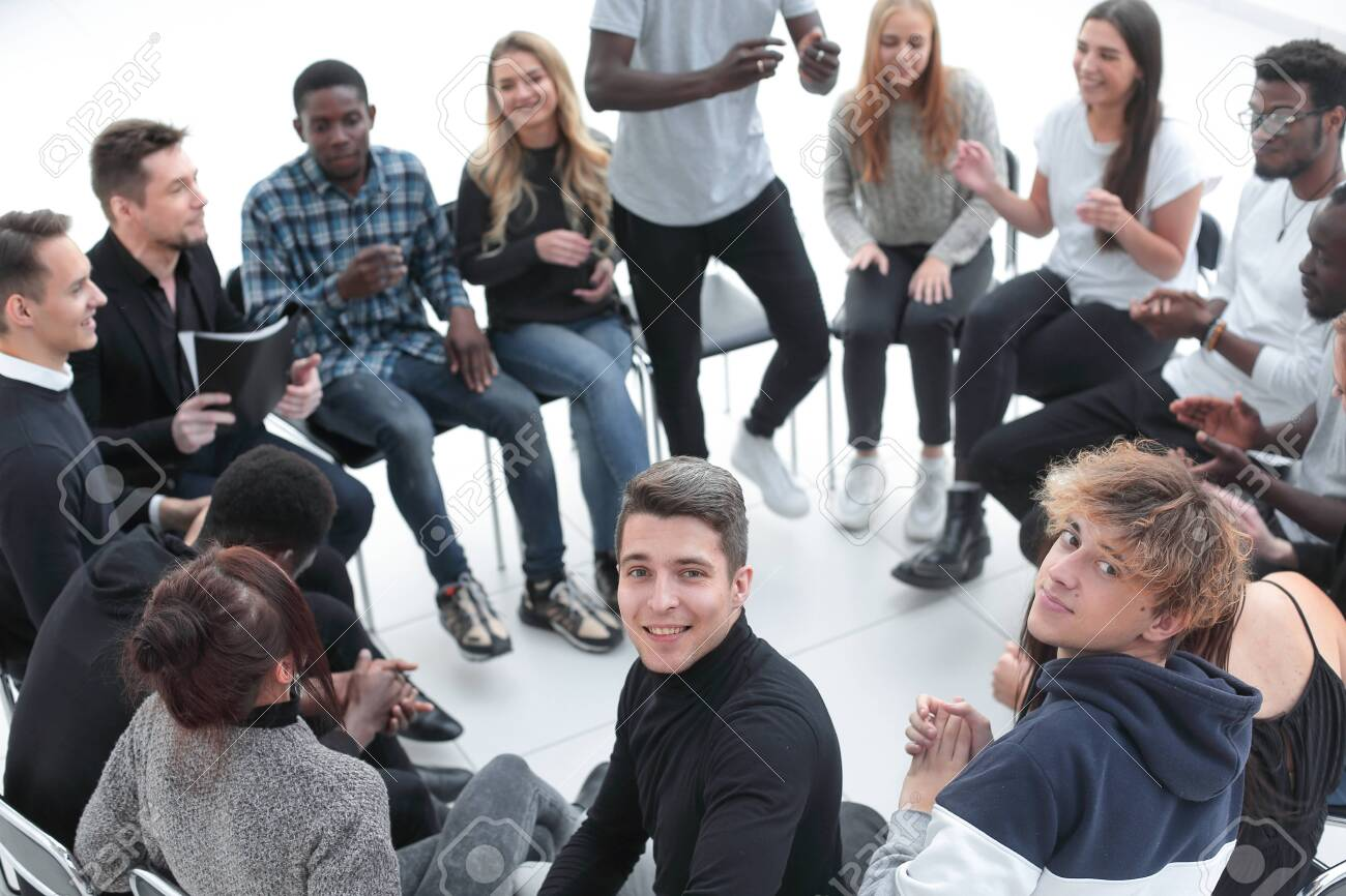 smiling young man sitting in a circle of friends - 147641118
