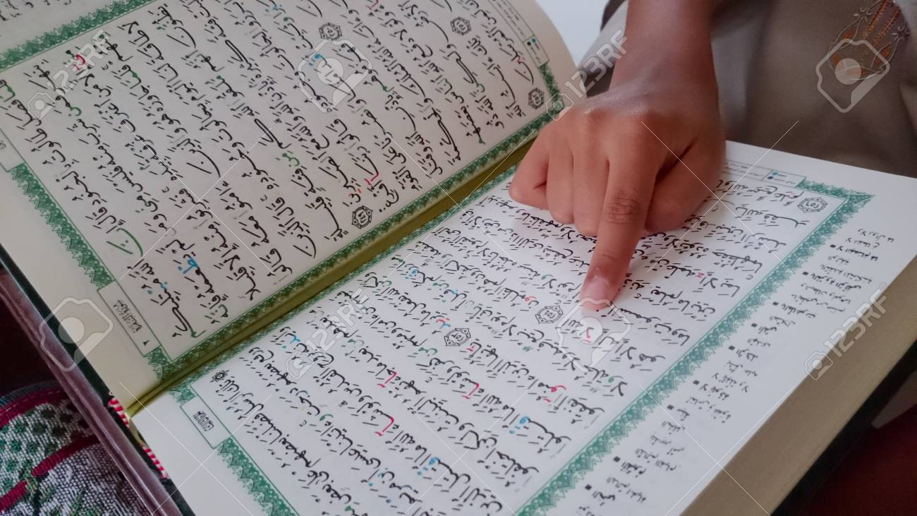 The kid of muslim reading a holy Quran during Ramadan month
