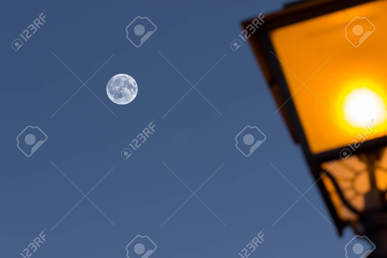 Una Lámpara En La Noche Con Una Luna En Cuarto Creciente En El Fondo ...