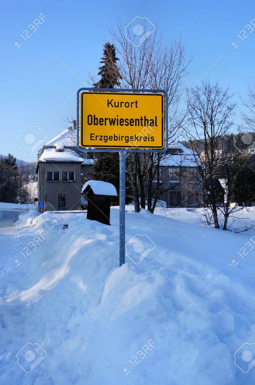Ortsschild Von Oberwiesenthal Im Erzgebirge, Gelbes Schild, Hauser ...