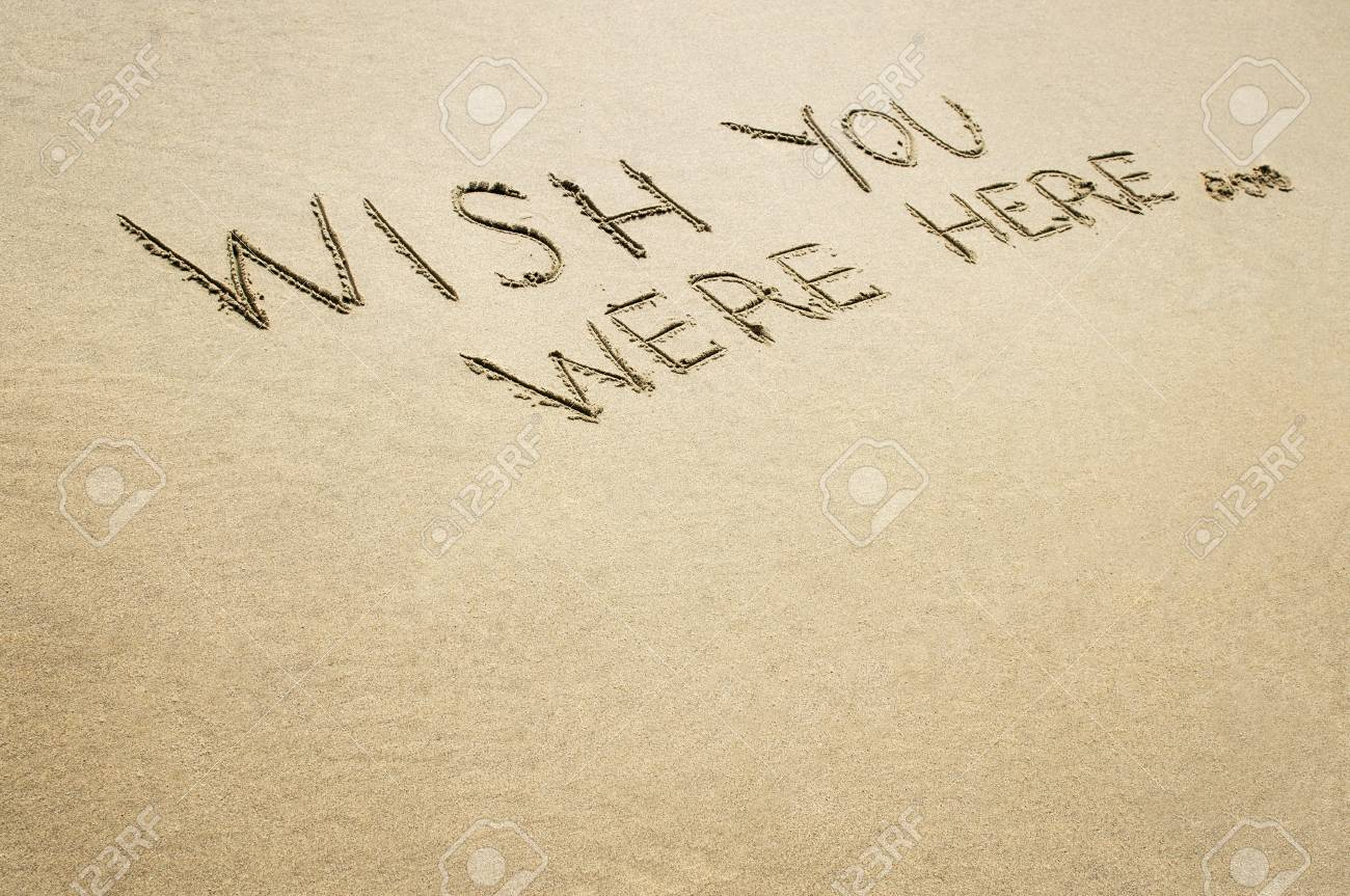 Words wish you were here written in the sand at the beach