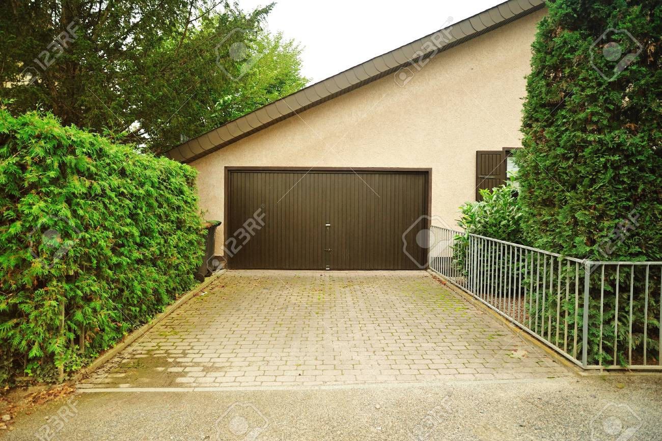 House Garage For Vehicles. Private Garage Near The House With Automatic  Doors And Paved Alley