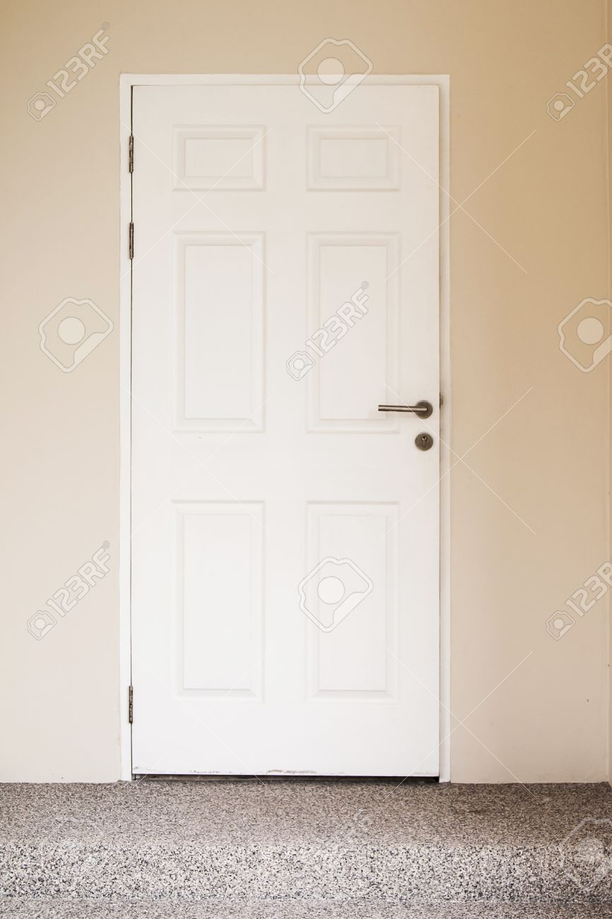 white wooden door on cream-colored walls and staircases stock