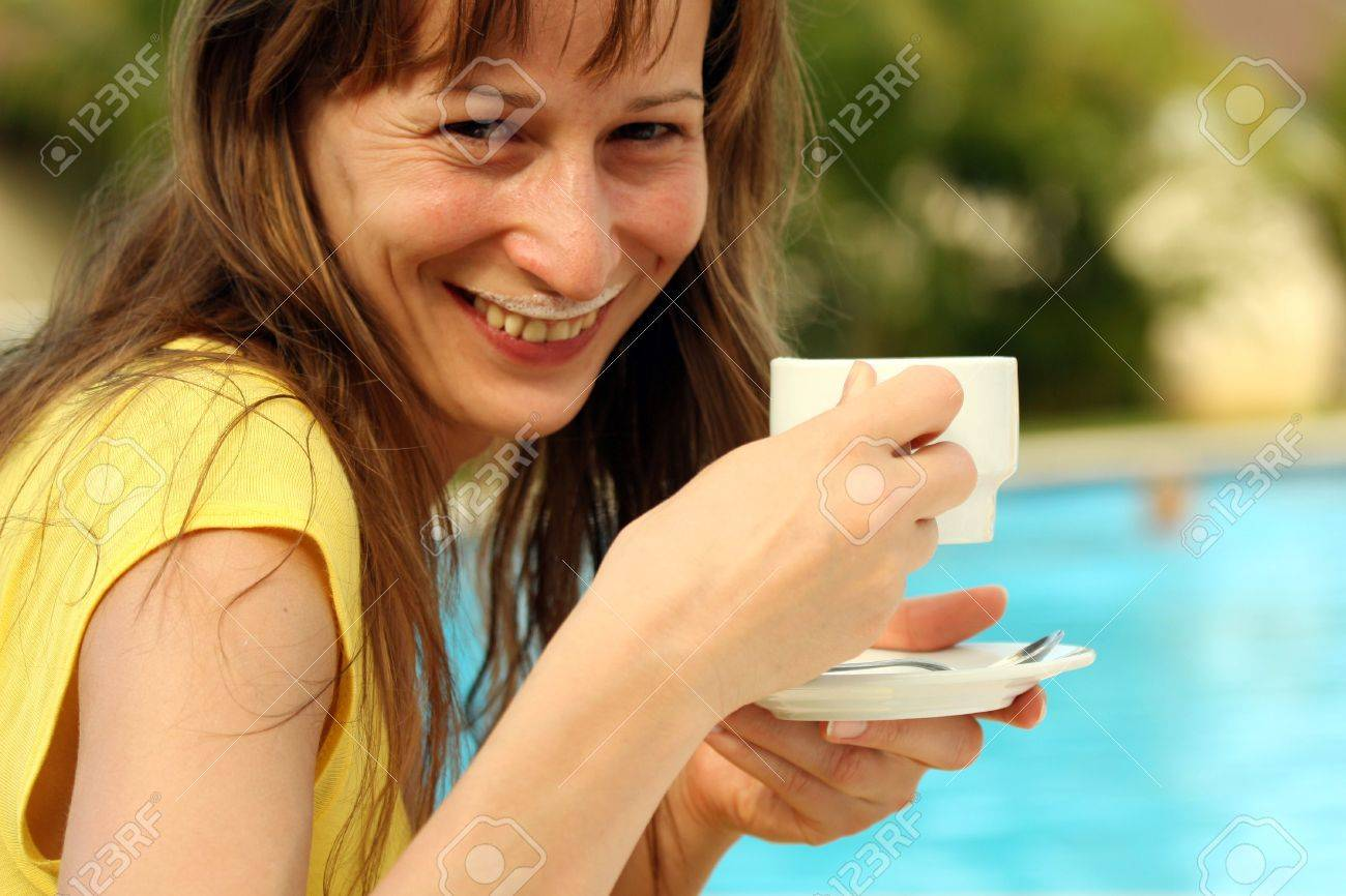 girl drinking a cup cappuccino by the pool Stock Photo - 2317865