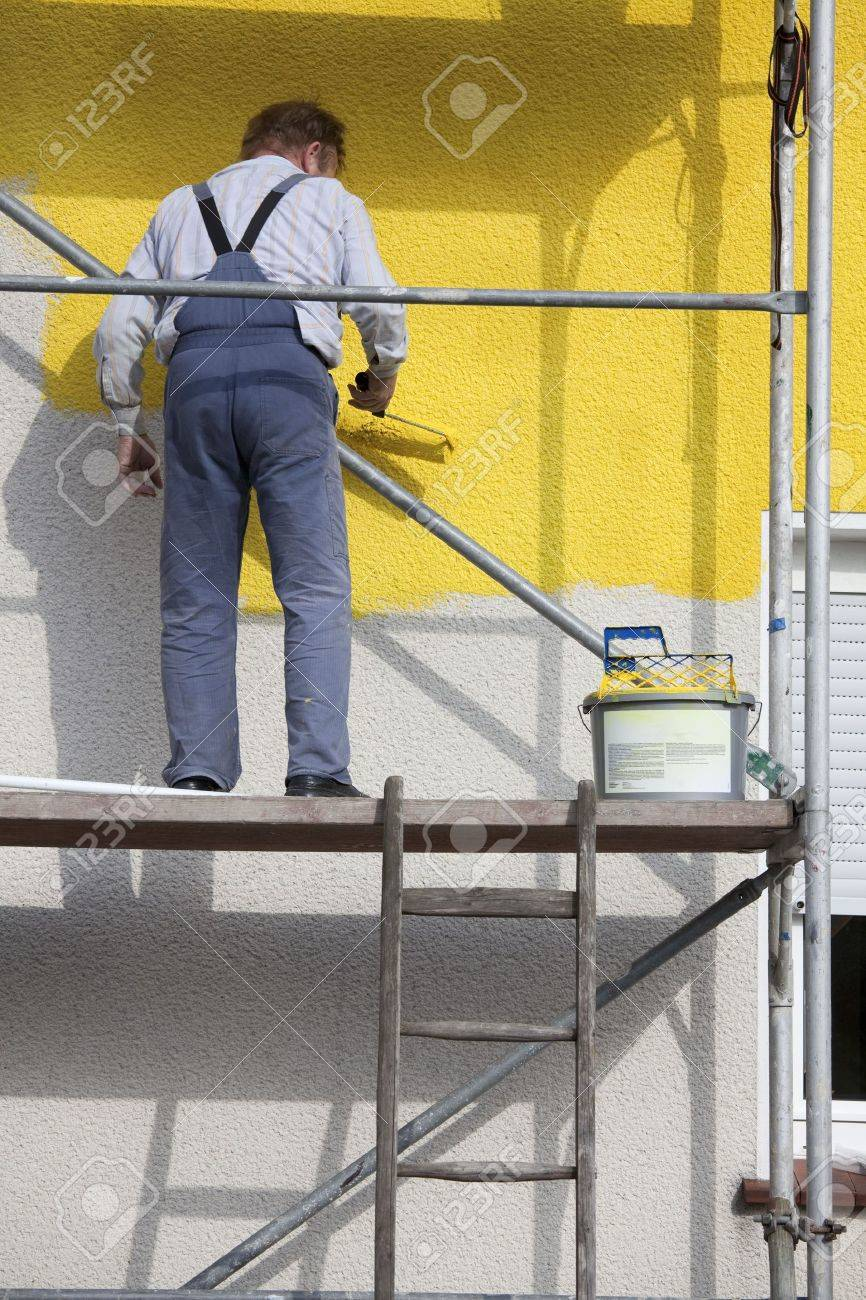 man on a scaffold painting house with roller stock photo picture