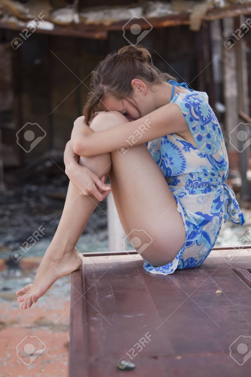 sad woman sitting in front of burned out house Stock Photo - 5629726