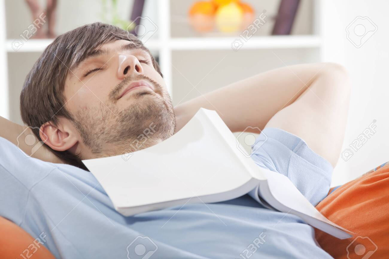 young man with book on his chest relaxing on the sofa Stock Photo - 8263021