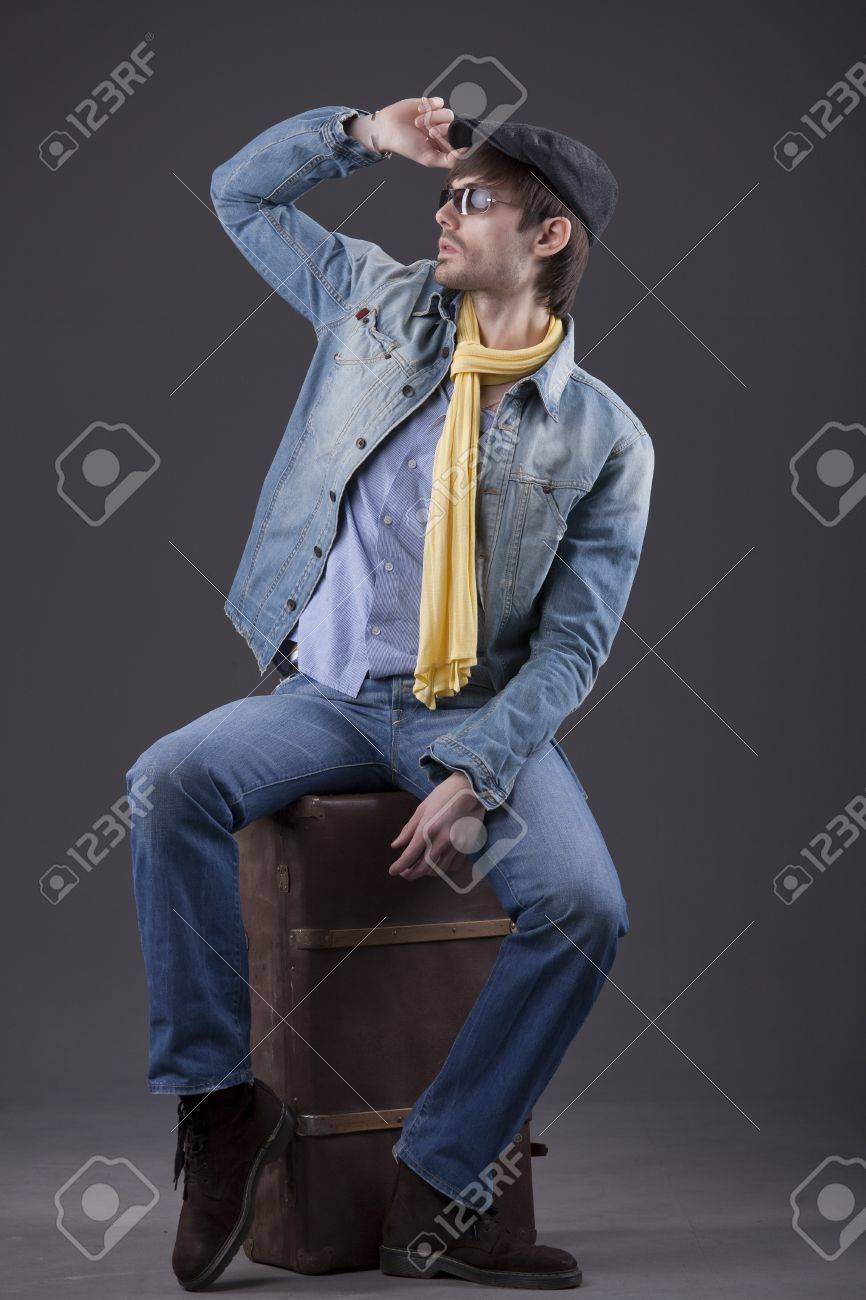 fashion man in denim clothes sitting on old suitcase Stock Photo - 8821054