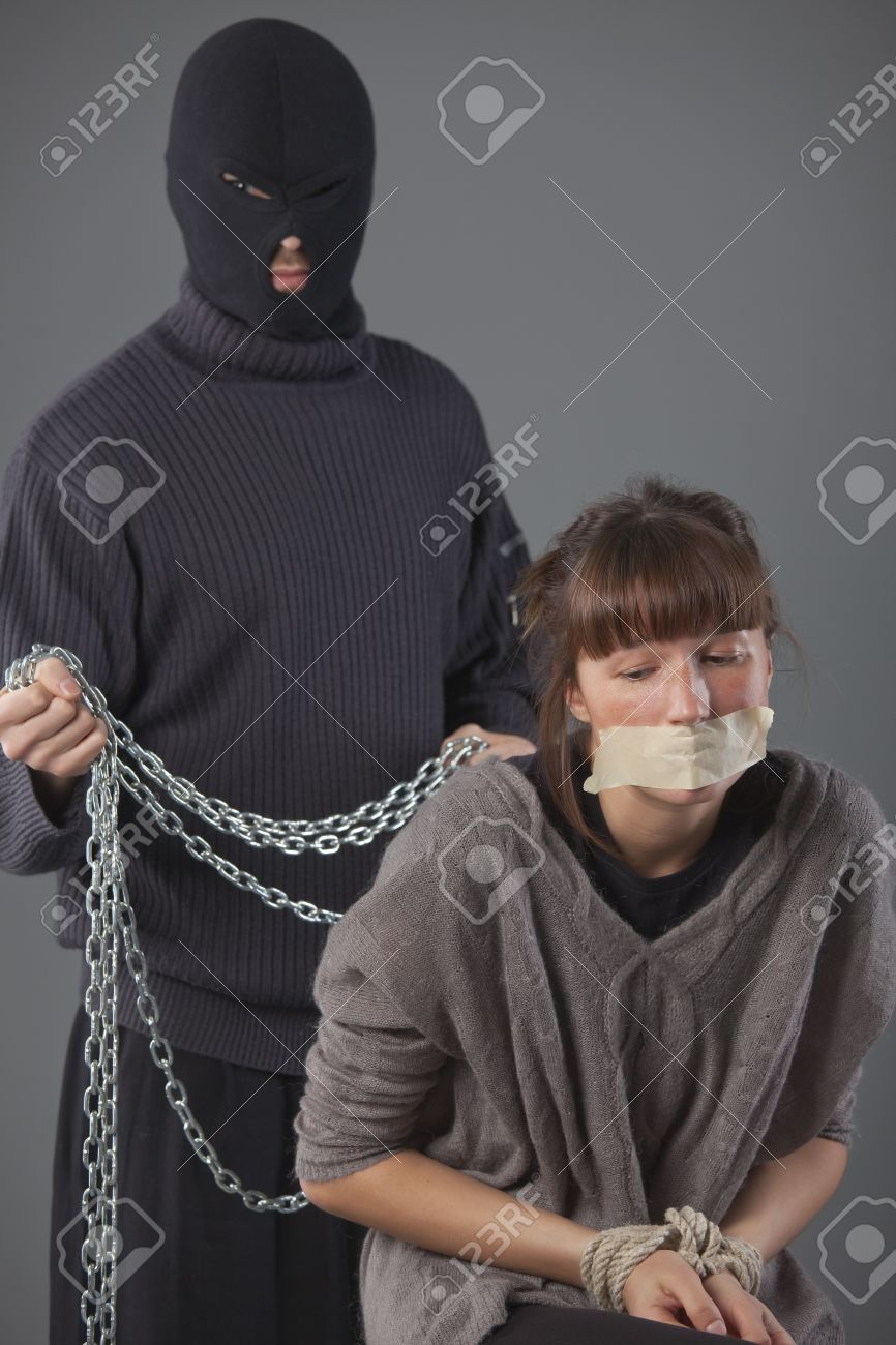 helpless kidnapped woman and hijacker with chain in background Stock Photo - 8905567