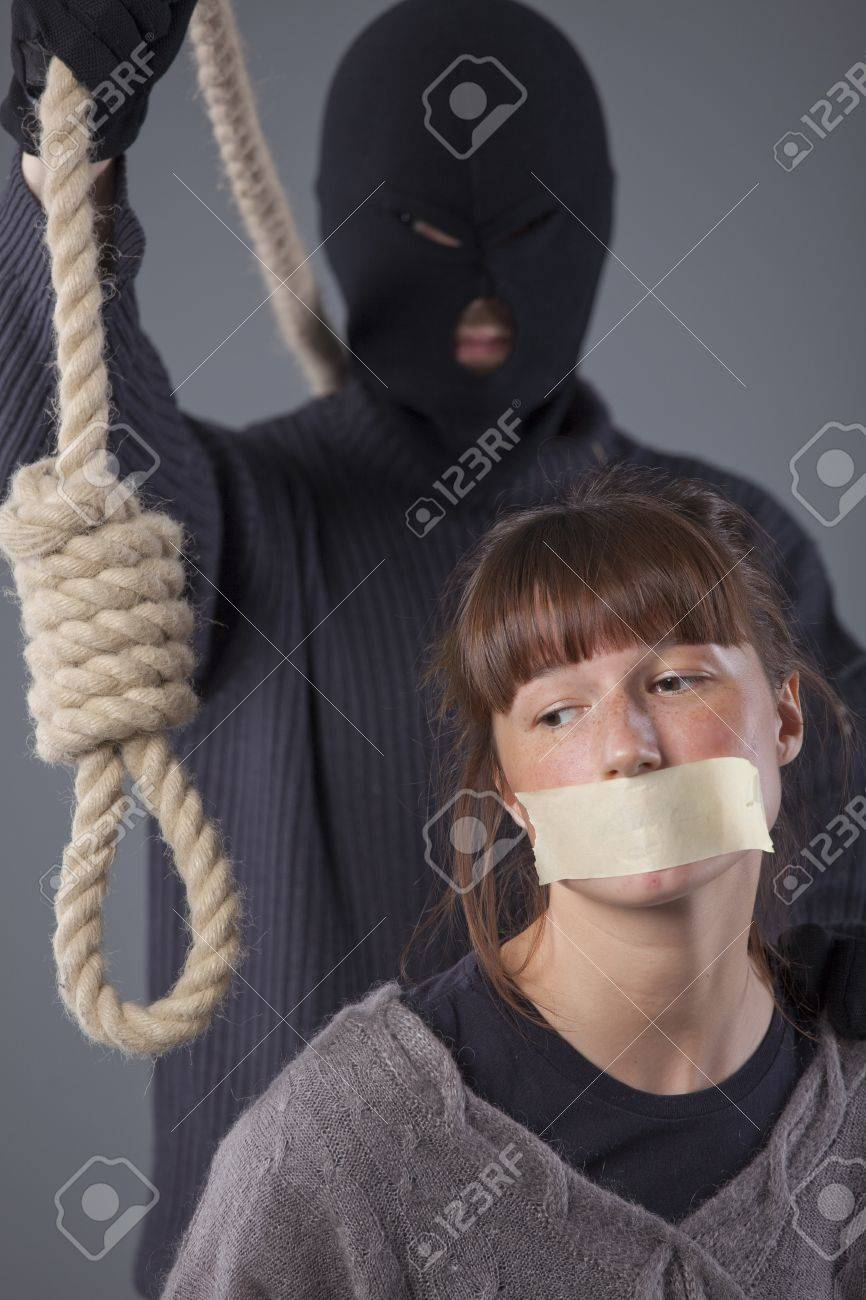 hangman with noose and female victim over grey background Stock Photo - 8905572