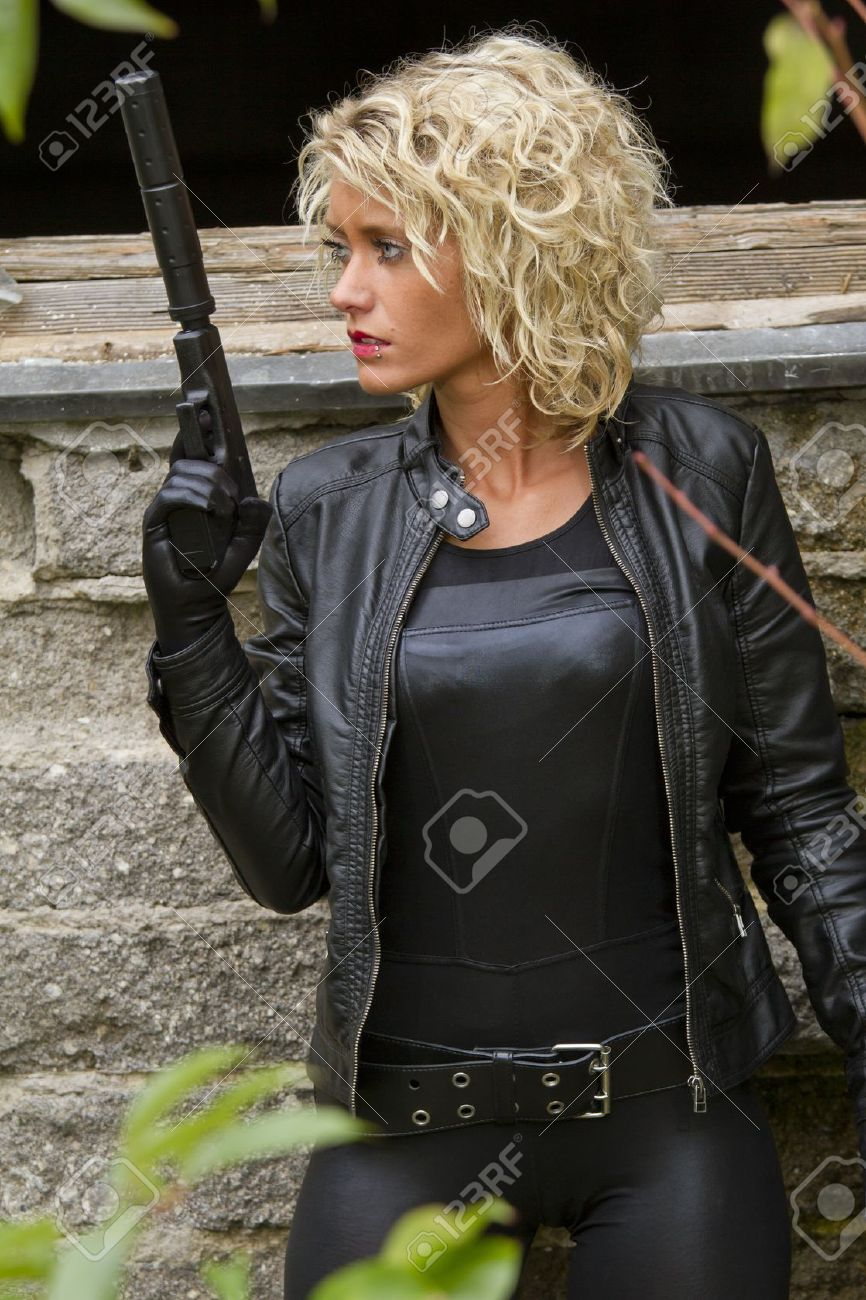Stock Photo Woman In Leather Catsuit And Gloves With A Silencer Gun Outdoor