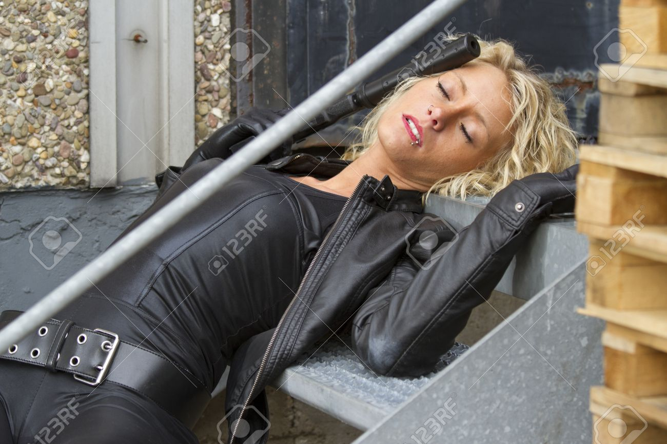 Crime scene - woman playing dead scene with a silencer handgun in her hand, lying on stairs Stock Photo - 15981519