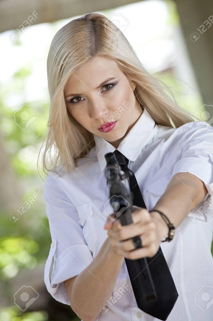 Mujer enojada en camisa blanca y corbata apuntando el arma en la cámara