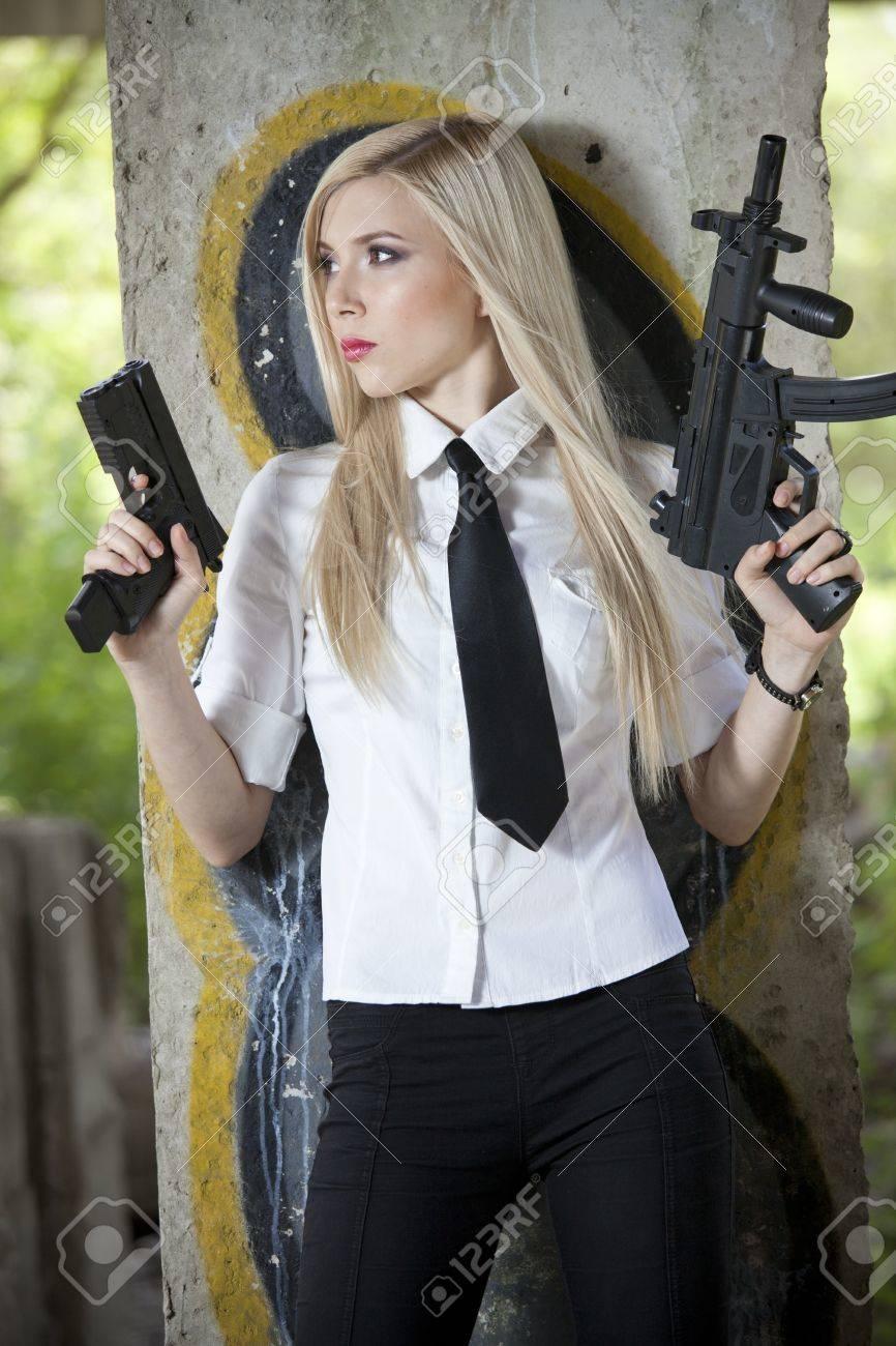 Mujer espía en camisa y corbata con dos armas de pie en la pared