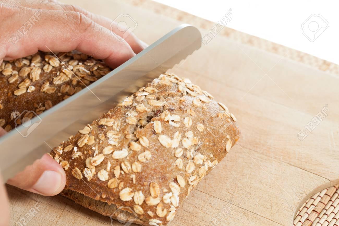 Man making a cut grain bread Stock Photo - 21598838