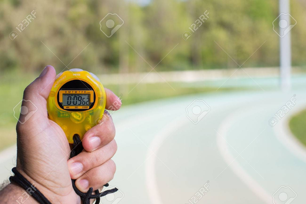 Coach clocking times in a running track - 27421604