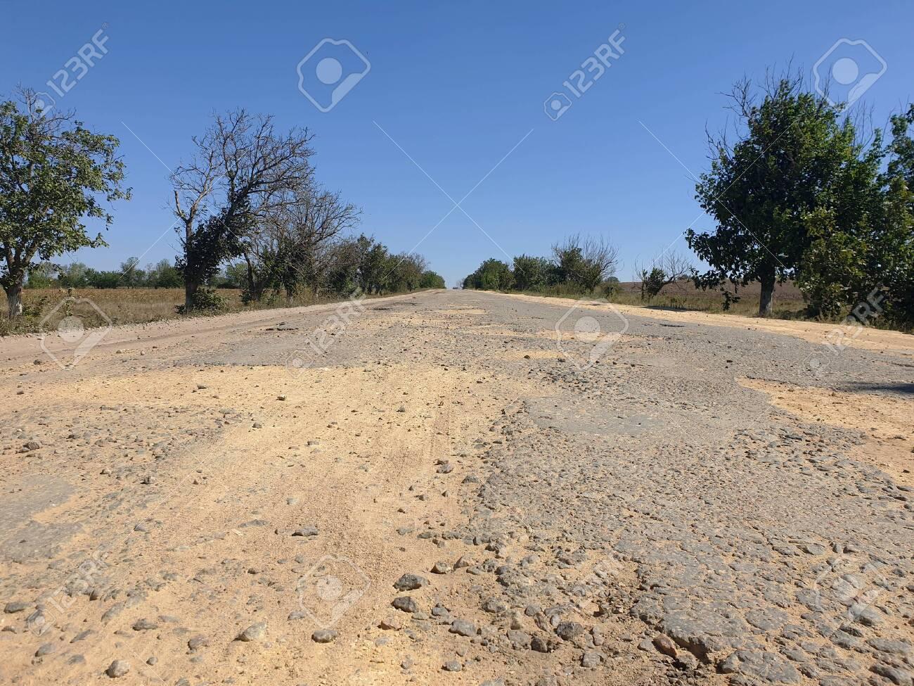 Dangerous road, potholes in the asphalt on the road - 155225398